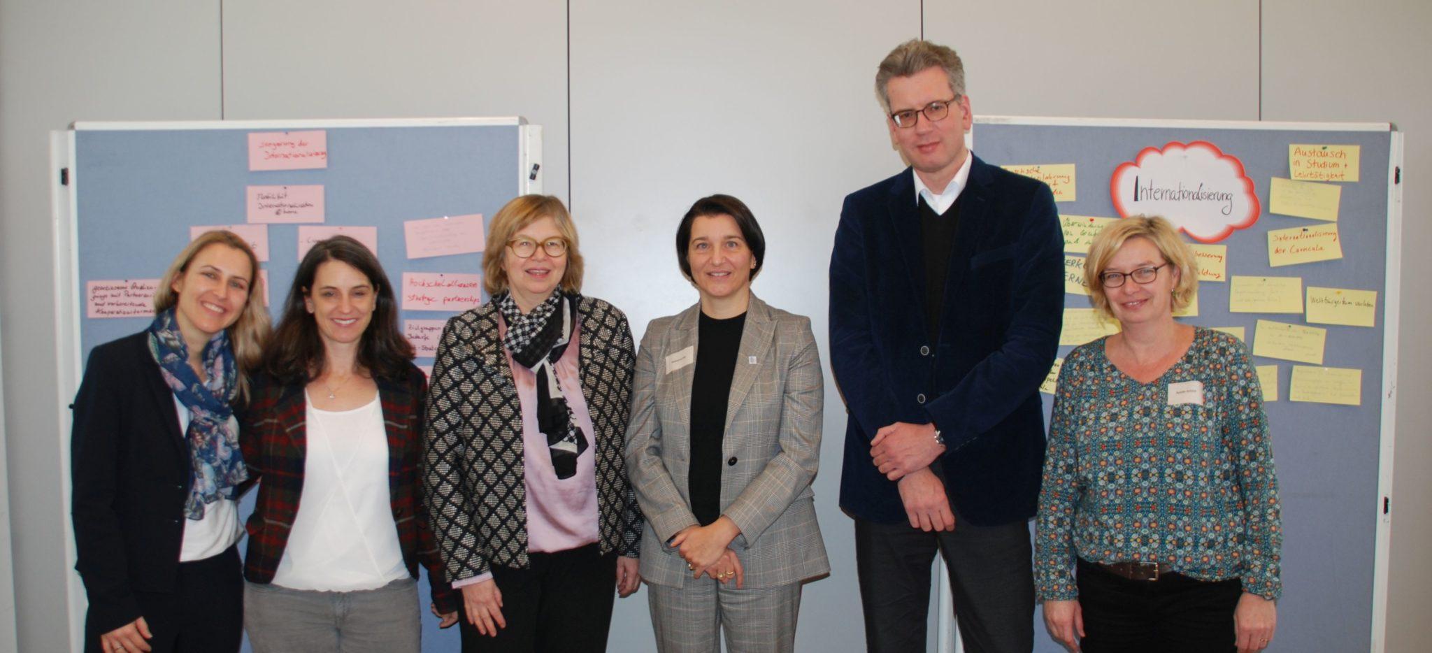 Gruppenfoto der Organisatorinnen und Referent*innen vor Stellwand mit Präsentation der Ergebnisse